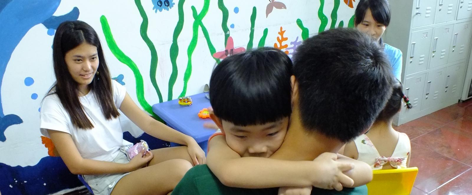 During teenage community volunteer work in China, a high school student hugs a young child in the classroom.